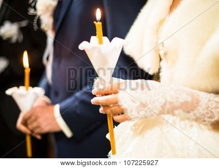 Wedding ceremony in orthodox church. Bride and groom holding the candles. Close up. poster