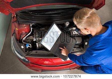 Mechanic Using Laptop To Repair Car