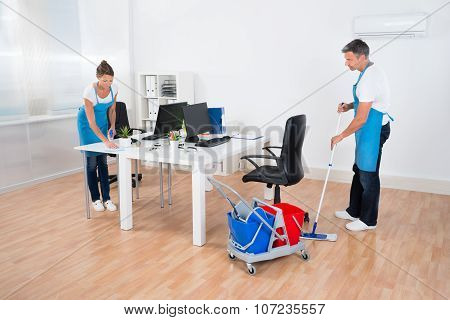 Two Cleaners With Cleaning Equipments Together Cleaning The Office poster