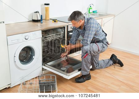 Full length of repairman checking dishwasher with digital multimeter in kitchen poster