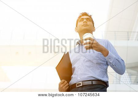 Asian Indian business man hand holding take away hot coffee cup and file folder in morning sunlight, outdoors modern office business concept.