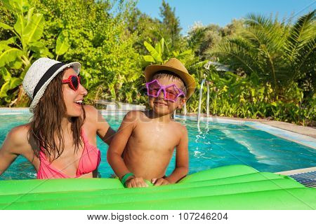 Mother and son wearing sunglasses lay on mattress
