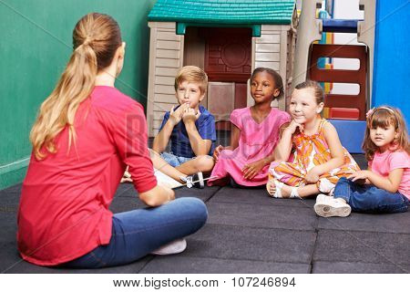 Discussion group of children in kindergarten talking to nursery teacher