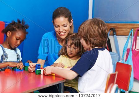 Children and nursery teacher building with blocks in kindergarten