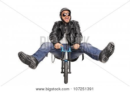 Studio shot of a silly young biker riding a very small bicycle and smiling isolated on white background