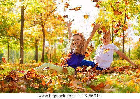 Happy boy and girl play with leaves in forest