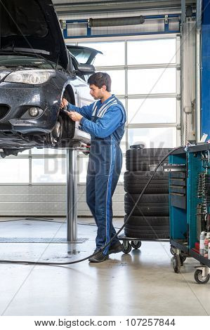 Mechanic, using a calipher, to check the thickness of a brake disk of a vehicle on a car lift. A stack of tires and a tools trolley behind him poster