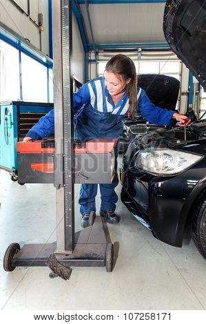 Mechanic, using an advanced measturing tool, to adjust the hight of a head light beam and high beam of a car as part of a MOT test poster