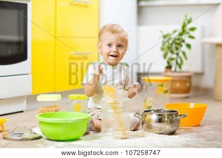 Playful Kid Boy With Face In Flour Surrounded Kitchenware And Foodstuffs