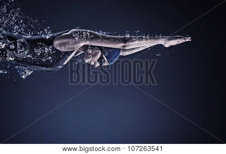 Young woman swimmer in cap and glasses under water