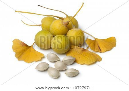 Ripe yellow Ginkgo biloba fruit, nuts and leaves on white background