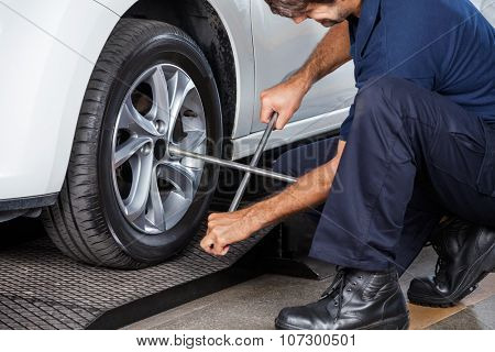 Male mechanic using rim wrench to fix car tire at garage poster