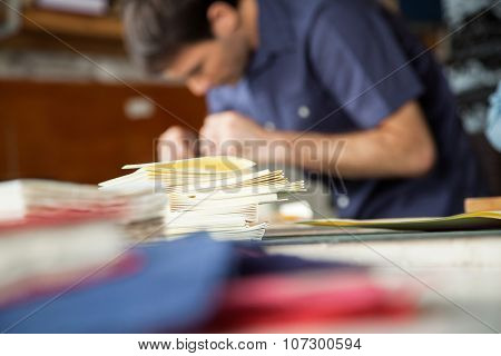 Closeup of stacked papers on table with man working in background at factory
