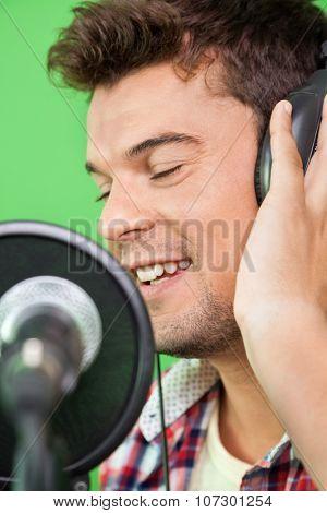 Closeup of smiling male singer performing in recording studio poster