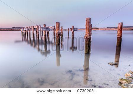 Old wooden pier at sunset broken in the river Barbate, Cadiz, Spain