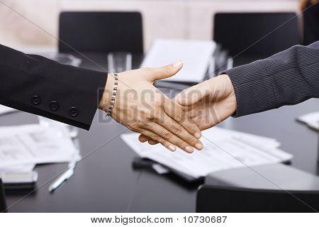 Apretón de manos empresarias sobre tabla