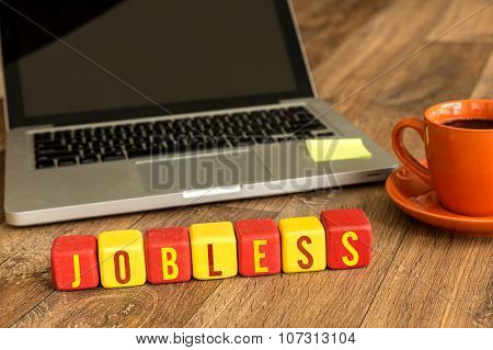 Jobless written on a wooden cube in front of a laptop