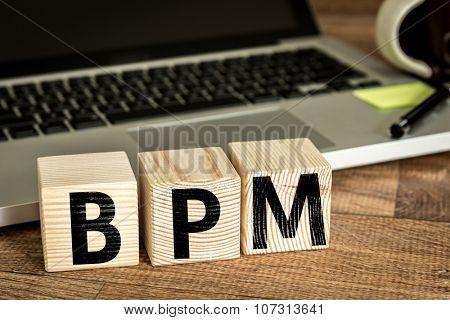 BPM (Business Process Management) written on a wooden cube in a office desk