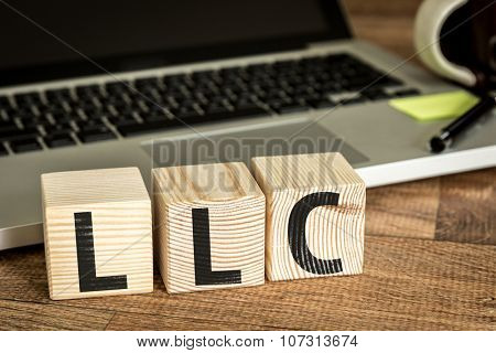 LLC (Limited Liability Company) written on a wooden cube in a office desk
