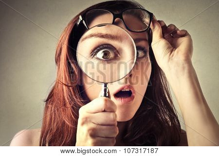 Shocked woman looking through a magnifying glass