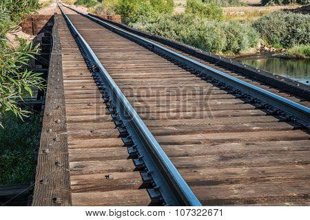 railroad tracks on trestle crossing a river - travel concept
