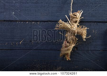 Photo closeup folk crafts one cross shaped Halloween rag voodoo doll made of sackcloth pierced with sticks on chest decoration hanging on rope over blue timber background horizontal picture poster