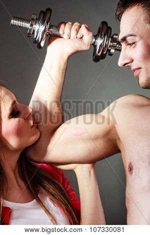 Bodybuilding. Strong man exercising with dumbbells. Closeup muscular guy flexing lifting weights girl looking admiringly kissing his biceps. poster