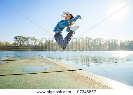happy young woman jumping high  on pontoon at lake in  tracksuit, sunny autumn day, full body shot