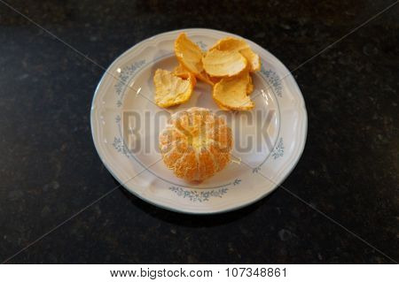 A peeled mandarin orange on a small white plate poster