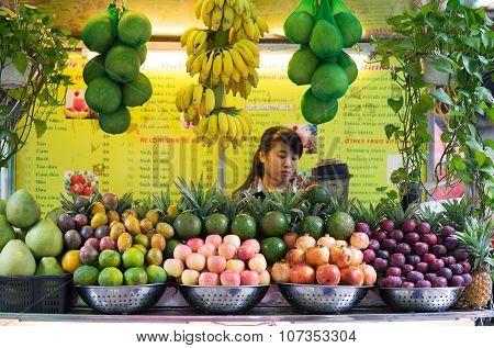 Vietnamese girl serving fresh tropical fruit juice on the sidewalk of a street in Hanoi