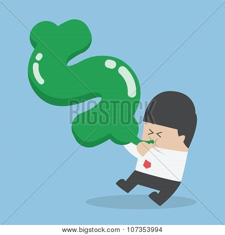Businessman Blowing Air Into Dollar Shape Balloon