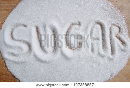The Word Sugar Written Into A Pile Of White Granulated Sugar Background