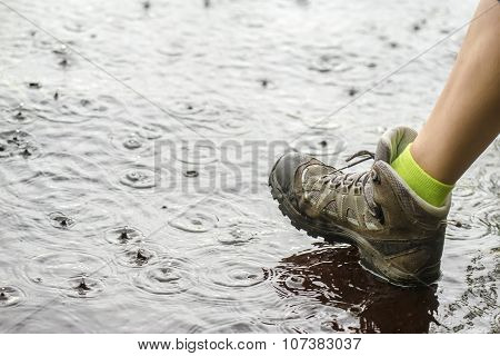 Person In Hiking Boots Walking On Water In The Rain