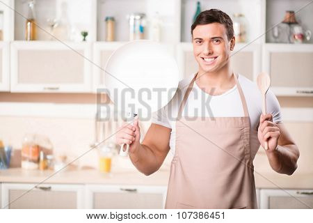 Young attractive cook with frying pan and spoon.