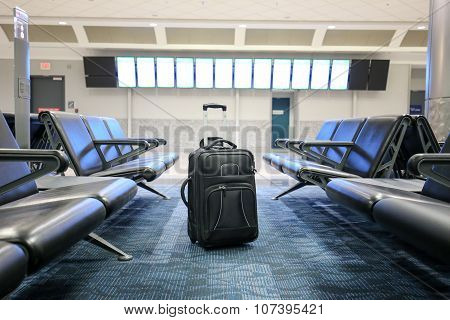 Black suitcase at an airport hall, as if lost.