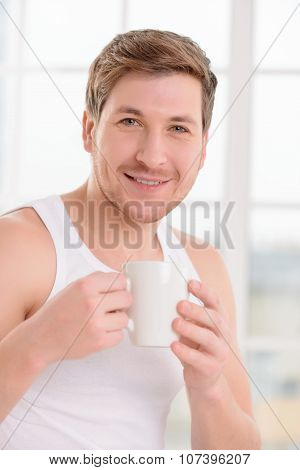 Young handsome guy enjoys his cup of coffee.