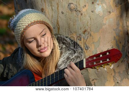 Girl With Woolen Cap And Guitar