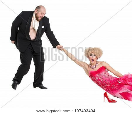 Eccentric Fat Man Dragging A Woman By The Hand Lying On Floor