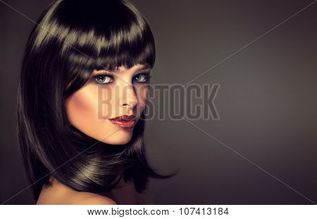 girl in profile with black straight shiny hair and bangs . Model brunette with hairstyle the care