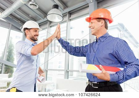 Cheerful male architect are greeting each other