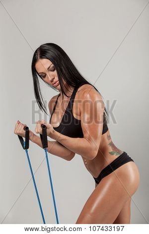 Sportswoman exercising with a resistance band on grey  background