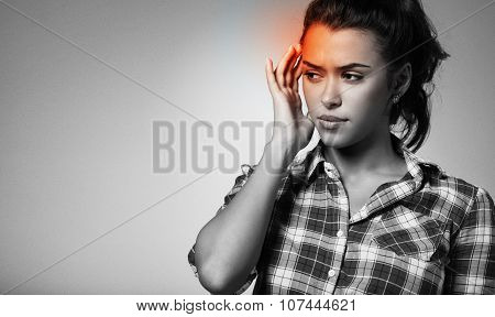 Closeup Portrait Of A Young Woman With Severe Headache Suffering Over Black Background.