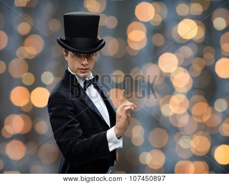 magic, performance, circus, show concept - magician in top hat pointing finger up over nigh lights background