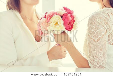 people, homosexuality, same-sex marriage and love concept - close up of happy married lesbian couple with flower bunch