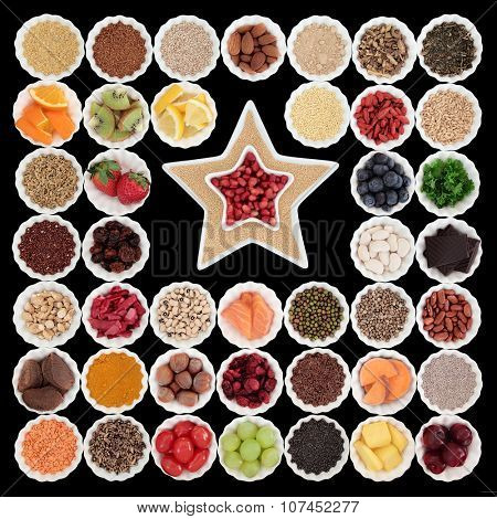 Large health and superfood collection in porcelain bowls with star shaped dishes over black background. High in vitamins and antioxidants.