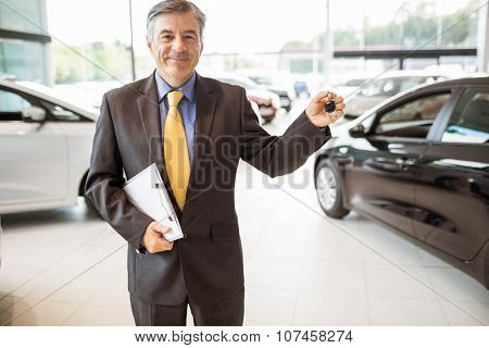 Smiling salesman holding a customer car key at new car showroom