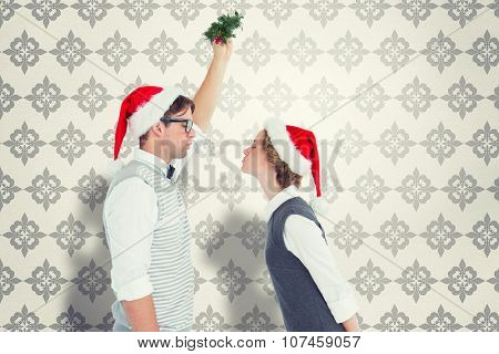 Geeky hipster kissing under mistletoe against grey wallpaper