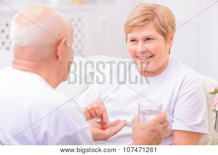 I will treat you. Pleasant adult loving man holding glass of water and giving pills to his wife while taking care of her poster
