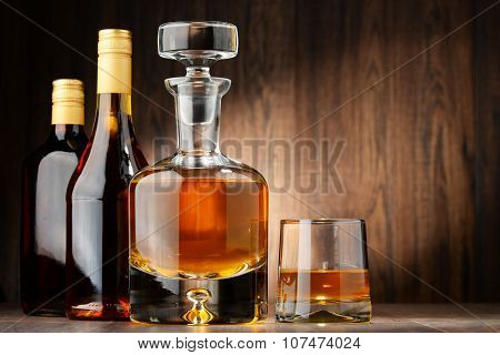 Bottles Of Assorted Alcoholic Beverages And Glass Of Whisky