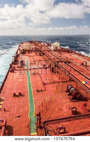 Big red deck of tanker ship under cloudy sky, while windy weather.